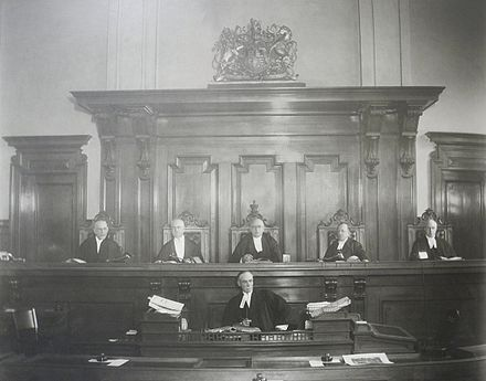 Justices of the Supreme Court of Ontario, with the court clerk seated below the bench. Documents and other forms are evidence is passed to the clerk before being handed to the judge. Photograph of justices of the Supreme Court of Ontario.jpg