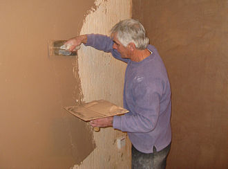 Plasterwork - A plasterer covering a wall, using a hawk (in his left hand) and trowel (in his right hand)