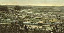 A tinted postcard depicts a town as seen from a hillside. It is laid out on a triangle of flat land between two converging streams. The larger and more distant of the two streams is flowing from mountains, while the smaller stream flows through farmland.