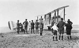 Military biplane parked at an airfield with a crowd of spectators
