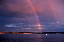 Primary and secondary rainbows are visible, as well as a reflected primary and a faintly visible reflected secondary.