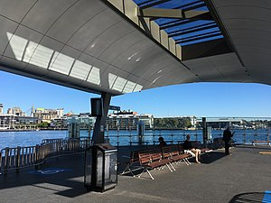 Barangaroo ferry wharf - Resting area for commuters at wharf 1. The berths of the wharf are located at the left and right side of the image.