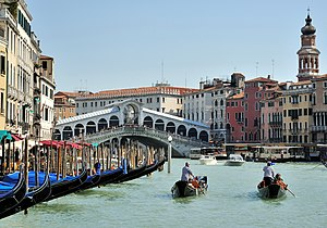 Grand Canal (Venice) - Two gondoliers pull out with clients on board from a row of gondolas on the Grand Canal near the Rialto Bridge.