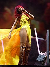 A woman with bright red long hair is singing. She wears a yellow dress with a long train, which is moved by the wind. Also the woman wears tights and brown boots.
