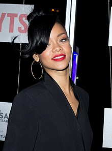 A brunette woman who is wearing a red lipstick and big earrings is smiling