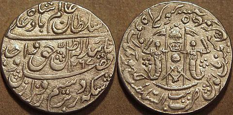 Silver rupee of Wajid Ali Shah, struck at Lucknow in AH 1267 (1850-51 CE) and showing the Awadh coat of arms on the reverse. The two figures holding the pennants are intended to be fish, seen also on the Awadh flag. Rupee of Wajid Ali Shah of Awadh.jpg