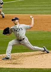 "A man in a gray baseball uniform reading ""Rays"" across the chest throws a baseball with his left hand from a dirt mound."