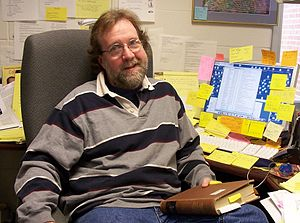 Professor Sean B Carroll sitting at his desk, holding a book, with lots of post-it notes glued everywhere.