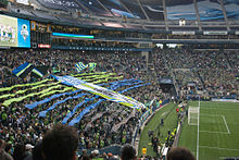 Fans waving flags and unfurling a large green and blue tifo behind a goal.
