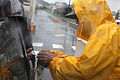 Security guard Atsushi Shimabukuro checks identification documents at the gate of U.S. Marine Corps Base Camp Smedley D. Butler in Okinawa, Japan, Oct. 28, 2010, as the area is hit by rain and wind from Typhoon 101028-M-VG363-022.jpg