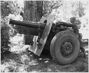 Sgt. James B. Aets uses a quadrant to determine the elevation of the 155mm. Hawitzer, while Cpl. Charles J. Hines... - NARA - 196472