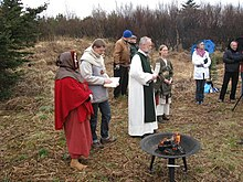 Eight people, all white, stand on heathland. Some of them are dressed in historical clothing akin to that worn in the medieval period.