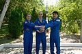 Soyuz MS-01 crew in front of a Soyuz rocket statue.jpg