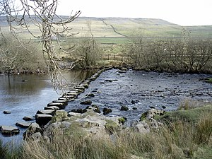 Stepping stone bridge over a stream between In...