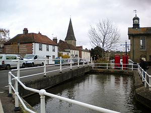 Stockbridge, Hampshire - One of the branches of the River Test which flow under the High Street with the spire of St Peter's in the background
