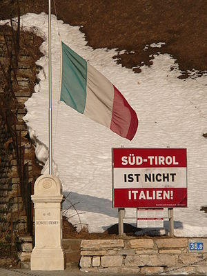 "Italianization of South Tyrol - Poster saying ""South Tyrol is not Italy!"" on the background of an Austrian flag. The poster is located in the Austrian side of the border, not in South Tyrol."