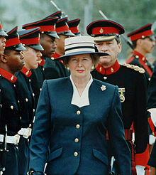 Thatcher walking in front of a line of military personnel, who are a mixture of races. Thatcher has a stern expression, dressed in a navy-coloured suit with buttons and a white hat.