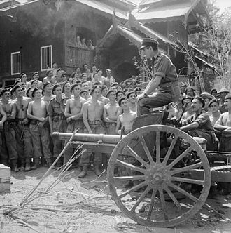 Type 95 75 mm field gun - Admiral Lord Louis Mountbatten, Supreme Allied Commander South East Asia, sits astride a captured Japanese 75 mm gun while addressing men of the Royal Armoured Corps in Mandalay, 21 March 1945