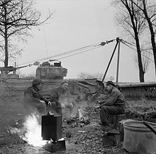 A tank crew brew up with a benghazi burner, at a stop in November 1944 during the Liberation of Holland. The tank behind is a Churchill AVRE, Armoured Vehicle Royal Engineers, carrying a portable Small Box Girder Bridge