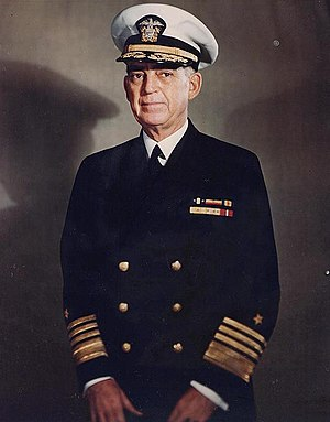 Man in dark blue suit and tie, wearing peaked cap and two rows of ribbons.