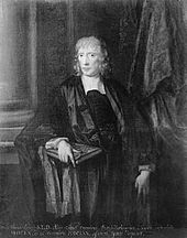 A man with light-coloured, slightly curly, hair. He is wearing black clothes and a black gown, and holds a large book in his right hand