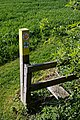 Three Forests Way signpost and stile off Tawney Lane, Stapleford Tawney, Essex, England.jpg