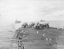 Black and white photograph with the deck of an aircraft carrier in the foreground and two other aircraft carriers in the background