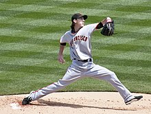Tim Lincecum, wearing a black baseball cap and grey baseball uniform with the words SAN FRANCISCO across, delivers a pitch