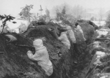 A group of soldiers with snowsuits stands in a trench, guns pointed to the left.