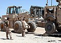 Two U.S. Marines, with 2nd Maintenance Battalion, 2nd Marine Logistics Group (Forward), assist another Marine, in a tractor, rubber tired; articulated steering, multipurpose vehicle forklift, in lifting a 110620-M-UV027-058.jpg