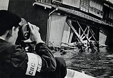 Black and white image of a cameraman in flood waters taking an image of a building's damaged façade.