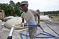 U.S. Army Sgt. William White, assigned to the 741st Quartermaster Company, South Carolina National Guard, carries a hose from a tactical water purification system to fill a water supply tank in Barnwell, S.C 130518-Z-XH297-004.jpg