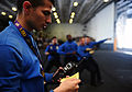 U.S. Navy Aviation Boatswain's Mate (Handling) Airman Zachary Castillo listens to a radio during firefighting training in the hangar bay aboard the aircraft carrier USS George H.W. Bush (CVN 77) in the Atlantic 130608-N-XE109-167.jpg