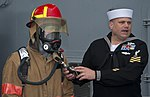 U.S. Navy Information Systems Technician 1st Class Christopher Cookson, right, instructs the Latvian Youth Guard on how to don firefighting gear June 10, 2013, during a tour aboard the U.S. 6th Fleet command 130610-N-ZL691-052.jpg