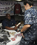 U.S. Navy Ship's Serviceman 1st Class Melvin Mallety, left, sells a cruise coin to a Sailor aboard the aircraft carrier USS Nimitz (CVN 68) Aug. 20, 2013, in the Gulf of Oman 130820-N-AZ866-131.jpg