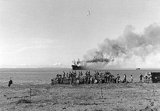 USS Alchiba (AKA-6) - Alchiba aground and afire off Lunga Point in November 1942.