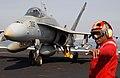 US Navy 030318-N-1810F-003 Chief Aviation Ordnanceman Anthony Andre Fobbs signals flight deck personnel to de-arm ordnance.jpg
