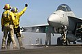 US Navy 030814-N-7732W-091 Aviation Boatswain's Mates signal to the pilot of an F-A-18F Super Hornet as the aircraft is directed onto one of four steam catapults aboard USS John C. Stennis (CVN-74).jpg