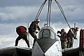 US Navy 050113-N-5781F-031 Crash-and-salvage personnel connect rigging cables to a F-14 Tomcat training aircraft prior to hoisting the aircraft during a flight deck fire drill.jpg