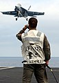 US Navy 050810-N-0226M-205 Lt. Kevin Robb, assigned to the Flying Eagles of Strike Fighter Squadron One Two Two (VFA-122), closely monitors the approach of a F-A-18F Super Hornet.jpg