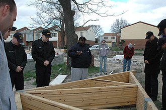 Church of God in Christ - Antonio Burke, pastor for the Center of Love Church of God in Christ (COGIC), leads Sailors from amphibious transport dock USS Nashville (LPD-13) in a prayer before building a house for Habitat for Humanity in Norfolk, Va.