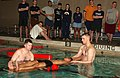 US Navy 070418-N-2143T-002 Lance Cpl. Brandon Coulter, Marine Combat Water Survival Instructor (MCWSI), and Master-at-Arms 1st Class Edwards Wolfe, from Marine Security Forces (MSF), remove Hospital Corpsman 3rd Class Carlos Ag.jpg