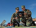 US Navy 081210-N-1226D-034 Engineman 2nd Class Zhiwei Li nd Chief Hospital Corpsman Kevin Avila use a Broadband Global Area Network portable satellite terminal.jpg