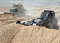US Navy 090305-N-1120L-078 Seabees assigned to Naval Mobile Construction Battalion (NMCB) 7 use an up-armored bulldozer and front end loader to build protective berms for a forward operating base.jpg