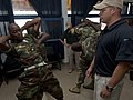 US Navy 100722-N-9589S-217 Master-at-Arms 2nd Class John Curry of Maritime Civil Affairs Security Training, Security Forces Assistance team, instructs members of the Cameroon navy on security procedures for personnel inspection.jpg