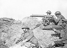 Four men in a barren landscape with a tripod-mounted machine gun