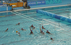 Water polo - A classic 4–2 man-up situation. The attacking white team has 4 players positioned on 2 metres, and 2 players positioned on 4 metres. The 5 outfield defending blue players try to block shots and prevent a goal being scored for the 20 seconds of man-down play. In the top left corner, the shot clock can be seen, showing 28 seconds remaining in the white attack.