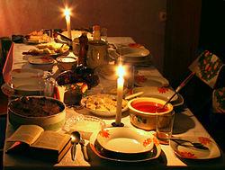 Stół przygotowany do wieczerzy wigilijnej dla czterech osób. Wśród potraw znajdują się: pieczony karp, makówki, barszcz oraz uszka, kutia z dżemem, pierogi z kapustą i grzybami, gołąbki, przygotowane są także opłatek, Biblia oraz nakrycie dla ewentualnego gościa.