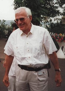 picture of a smiling man with white hair, wearing dark glasses