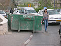 Woman walking around a dumpster.jpg
